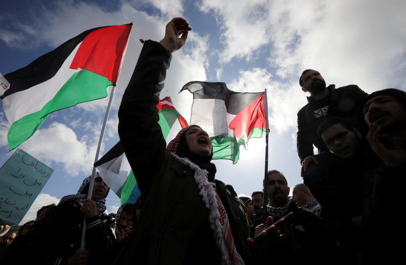 Protesters hold Jordanian and Palestinian flags and shout slogans during a protest against U.S. President Donald Trump's proposed Middle East peace plan, near the U.S. Embassy in Amman, Jordan, January 31, 2020. (photo credit: REUTERS)