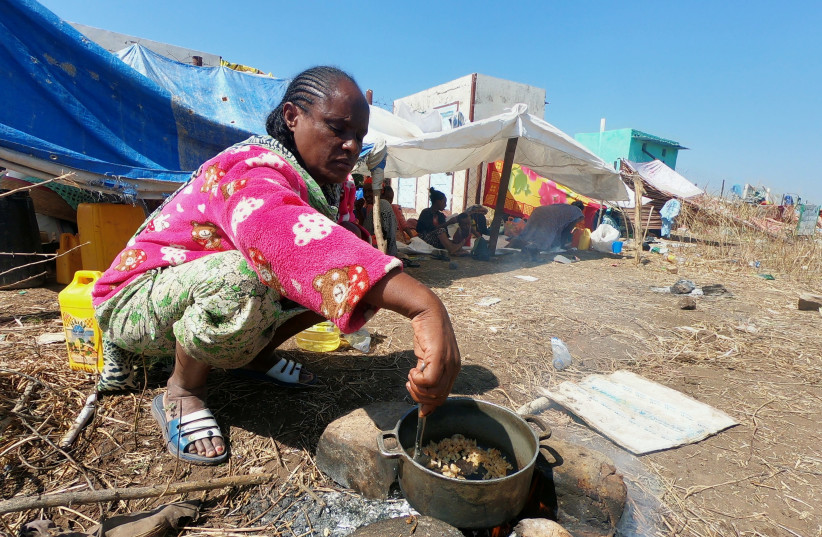 An Ethiopian who fled the ongoing fighting in Tigray region, prepares a meal in Hamdait village on the Sudan-Ethiopia border in eastern Kassala state, Sudan November 14, 2020. REUTERS/El Tayeb Siddig (photo credit: REUTERS/EL TAYEB SIDDIG)