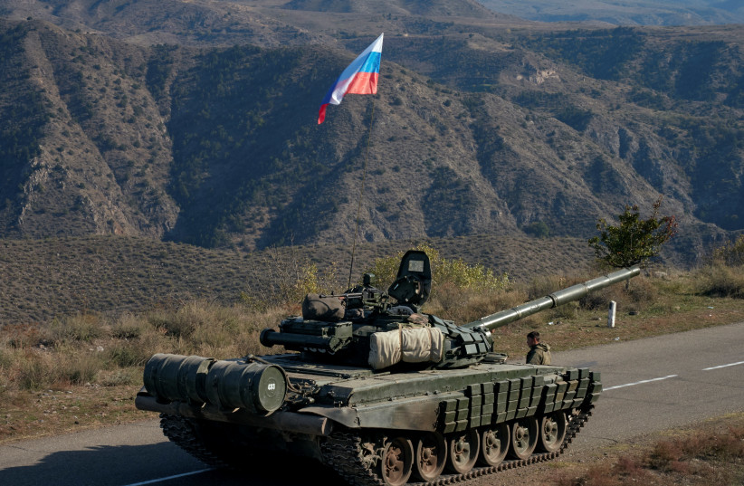 A service member of the Russian peacekeeping troops stands next to a tank near the border with Armenia, following the signing of a deal to end the military conflict between Azerbaijan and ethnic Armenian forces, in the region of Nagorno-Karabakh, November 10, 2020 (photo credit: REUTERS/FRANCESCO BREMBATI)