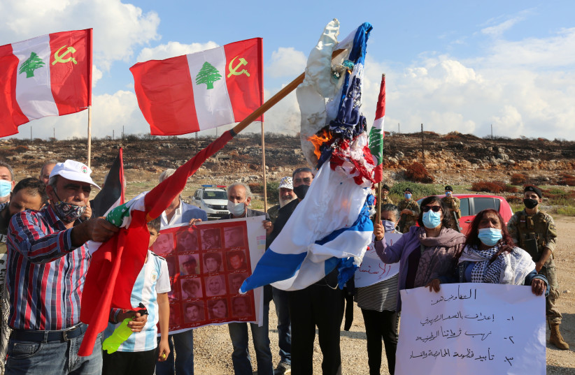 BURNING AMERICAN and Israeli flags in protest of talks on disputed maritime borders with Israel, in Naqoura near the Lebanese-Israeli border, November 11. (photo credit: AZIZ TAHER/REUTERS)