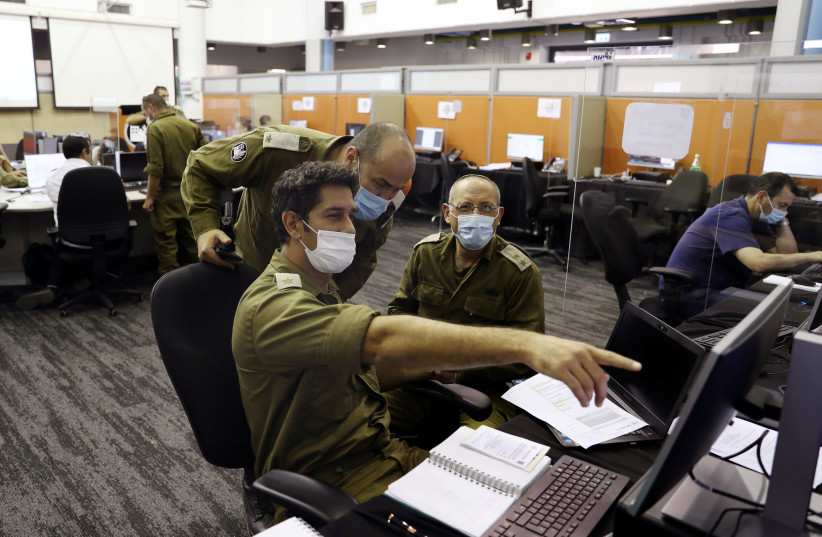 Israeli soldiers at the IDF Corona Task Force Headquarters as they conduct epidemiological investigations as part of the army's effort to trace chains of infection to curb the spread of coronavirus, Ramle, Israel, September 17, 2020 (photo credit: RONEN ZVULUN/REUTERS)
