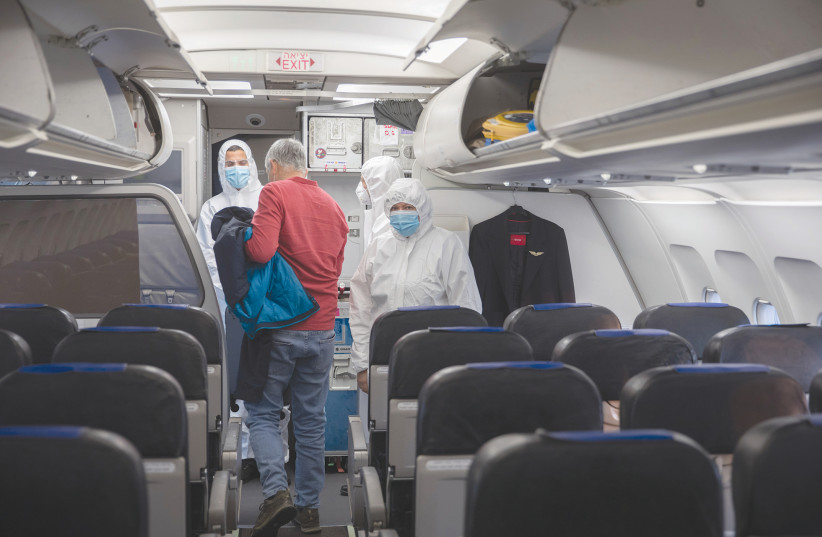 ISRAIR FLIGHT attendants wear full protective gear as they help a passenger disembark in Belgrade earlier this month.  (photo credit: NATI SHOHAT/FLASH90)