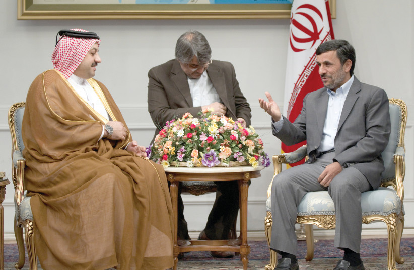 Iranian President Mahmoud Ahmadinejad (right) gestures as he attends an official meeting with Qatar's Foreign Minister Adviser Khalid Mohammad al-Atiyeh in Tehran on October 13, 2011 (photo credit: MORTEZA NIKOUBAZI/ REUTERS)