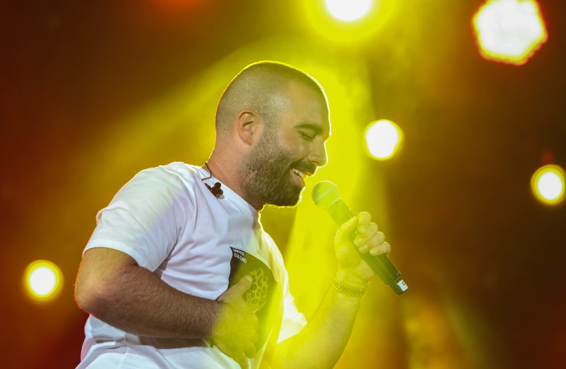 Israeli singer Omer Adam performs live at the annual Kleizmer Festival in the northern Israeli city of Tzfat, on August 14, 2019. (photo credit: DAVID COHEN/FLASH 90)