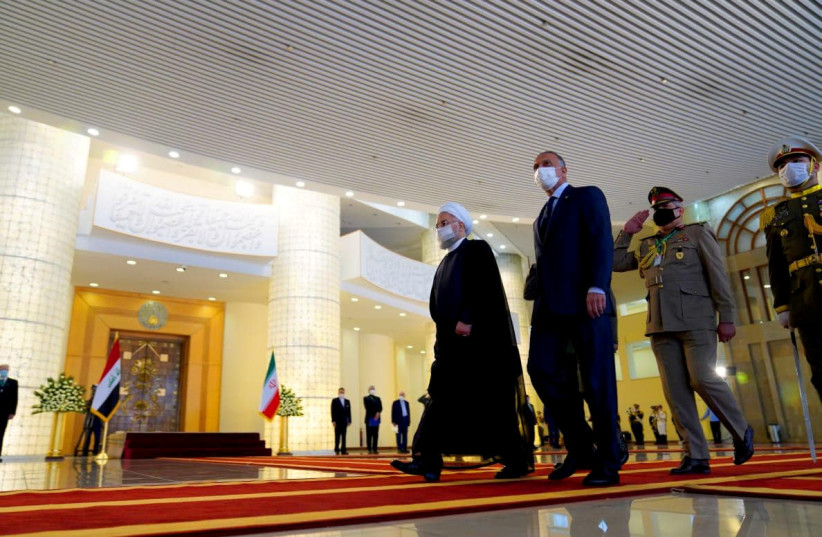 Iranian President Hassan Rouhani welcomes Iraqi Prime Minister Mustafa al-Kadhimi as they wear protective masks, in Tehran, Iran, July 21, 2020. (photo credit: IRAQI PRIME MINISTER MEDIA OFFICE/HANDOUT VIA REUTERS)