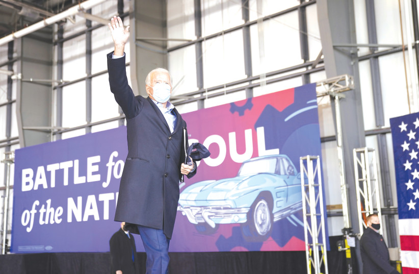 Joe Biden salutes supporters next to the slogan 'Battle for the soul of the nation' during a pre-election event in Cleveland, Ohio, on November 2. (photo credit: KEVIN LAMARQUE/REUTERS)