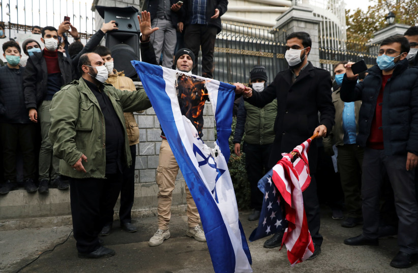 Protesters burn the US and Israeli flags during a demonstration against the the killing of Mohsen Fakhrizadeh, Iran's top nuclear scientist, in Tehran, Iran, November 28, 2020. (photo credit: MAJID ASGARIPOUR/WANA (WEST ASIA NEWS AGENCY) VIA REUTERS)
