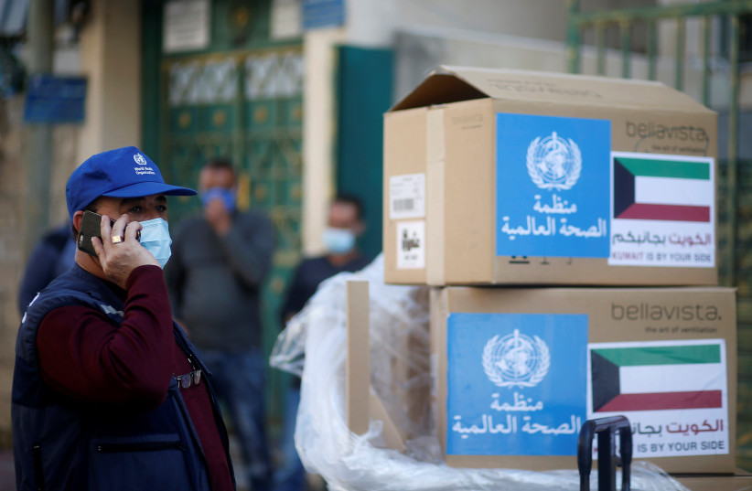Abdelnaser Soboh, Emergency Health Lead in the World Health Organization's Gaza sub-office, stands next to boxes containing ventilators delivered by the World Health Organization (WHO) and donated by Kuwait, in Gaza City November 29, 2020. (photo credit: REUTERS/MOHAMMED SALEM)