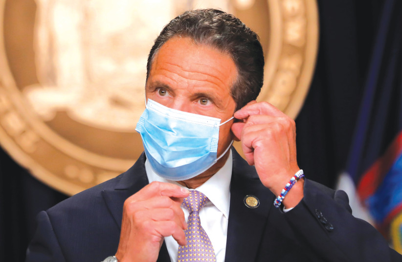 NEW YORK Gov. Andrew Cuomo wears a face mask as he arrives at a daily briefing in New York City in July. (photo credit: MIKE SEGAR / REUTERS)