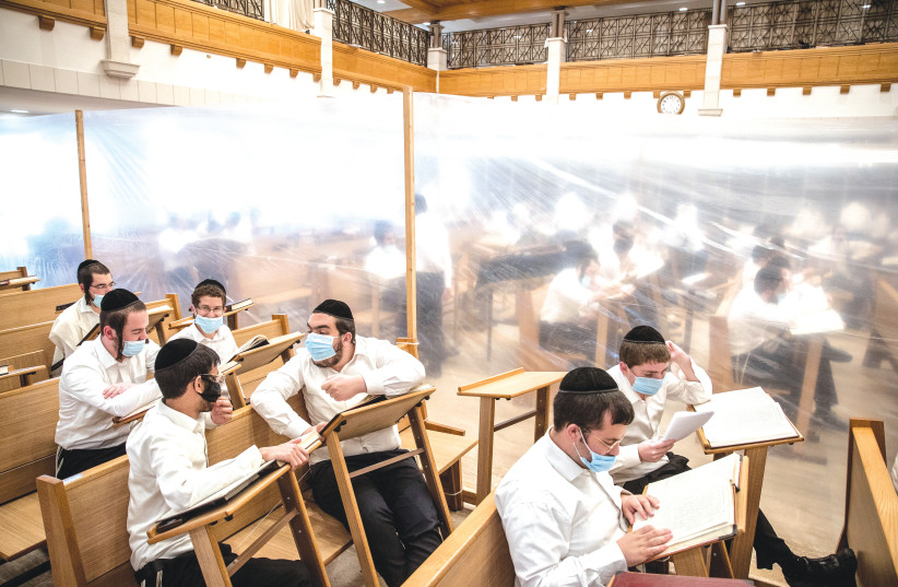 STUDENTS STUDY in separation compartments at the Kamenitz Yeshiva in Jerusalem in September to prevent the spread of COVID-19. (photo credit: YONATAN SINDEL/FLASH 90)