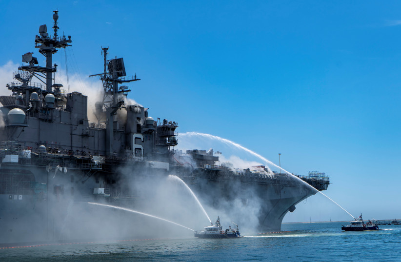 Port of San Diego Harbor Police Department boats combat a fire on board the US Navy amphibious assault ship USS Bonhomme Richard at Naval Base San Diego, California, US July 12, 2020. (photo credit: US NAVY/MASS COMMUNICATION SPECIALIST 3RD CLASS CHRISTINA ROSS/HANDOUT VIA REUTERS)