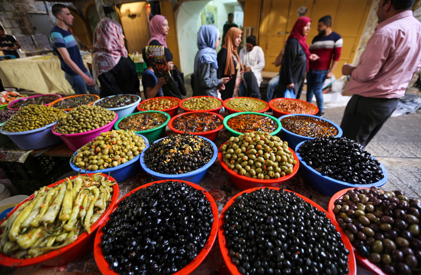 Palestinians buy food during the holy month of Ramadan, at a market in the West Bank city of Hebron, May 22, 2019. (photo credit: WISAM HASHLAMOUN/FLASH90)