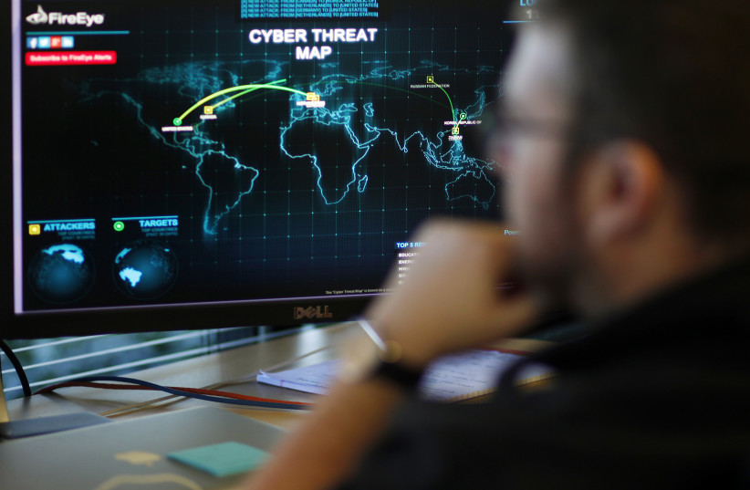 An information analyst works in front of a screen showing a near real-time map tracking cyber threats; California, December 29, 2014 (photo credit: REUTERS/BECK DIEFENBACH)