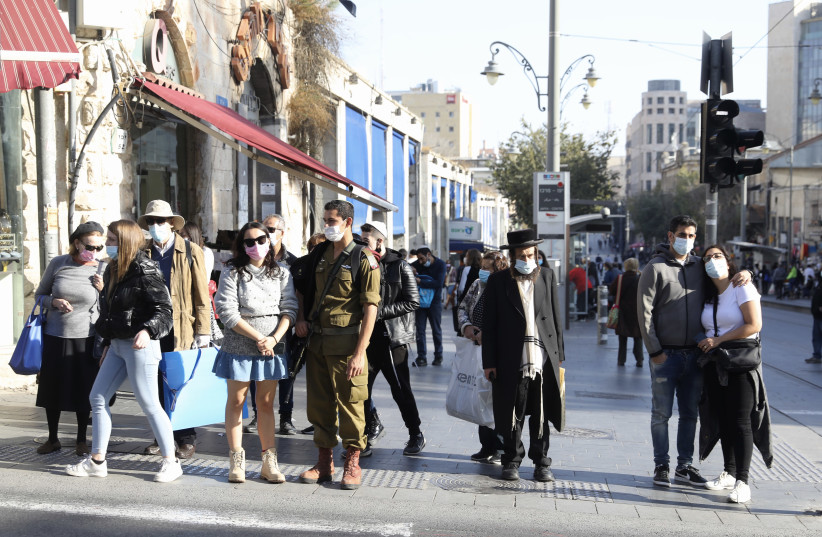 Israelis are seen in Jerusalem wearing masks in accordance with coronavirus restrictions, on December 1, 2020. (photo credit: MARC ISRAEL SELLEM/THE JERUSALEM POST)