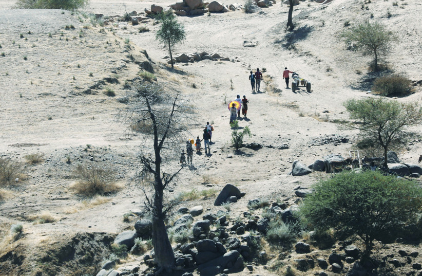 ETHIOPIANS FLEEING from the Tigray region walk toward a river to cross from Ethiopia to Sudan earlier this week. (photo credit: REUTERS)