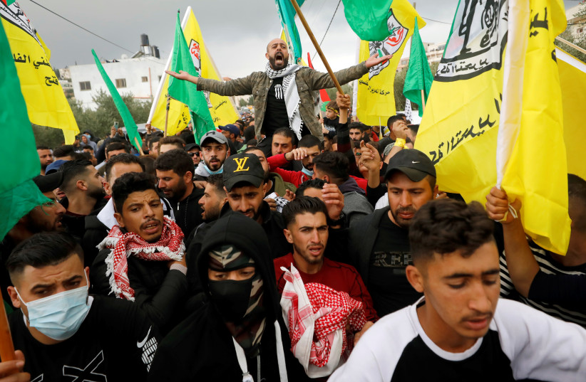 Mourners take part in the funeral of Palestinian teenager Ali Abu Alia in al-Mughayyir village near Ramallah in the West Bank, December 5, 2020. (photo credit: MOHAMAD TOROKMAN/REUTERS)