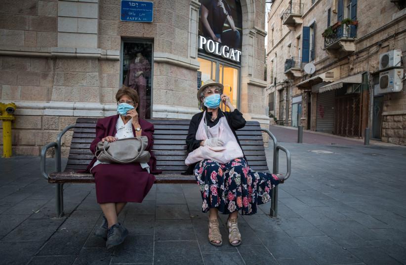 Two elderly women sit on a bench on Jaffa Street in downtown Jerusalem on October 26, 2020.  (photo credit: NATI SHOHAT/FLASH90)