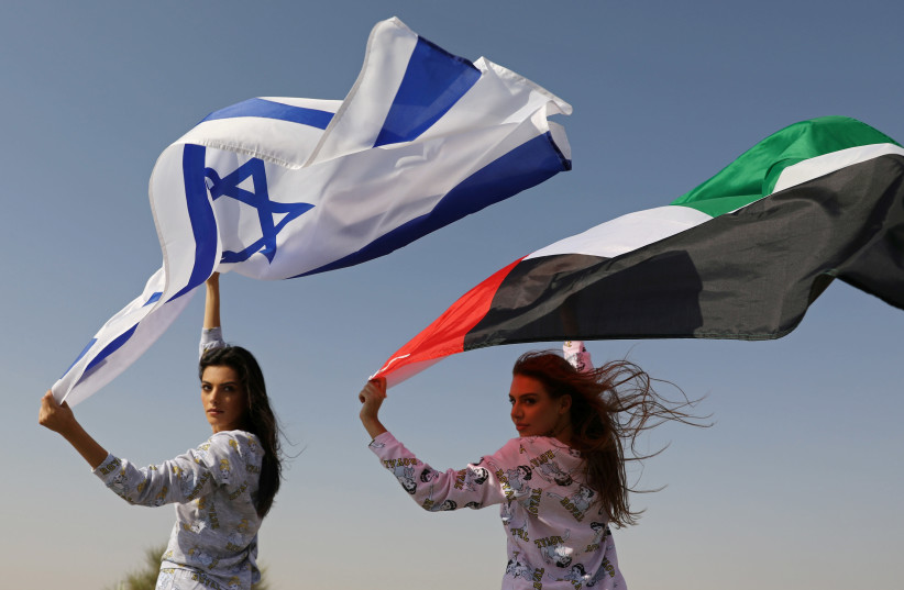 Israeli model May Tager, holding an Israeli flag, poses with Dubai-resident model Anastasia, holding an Emirati flag, during a photoshoot for FIX's Princess Collection in Dubai, United Arab Emirates, September 8, 2020. (photo credit: REUTERS/CHRISTOPHER PIKE)
