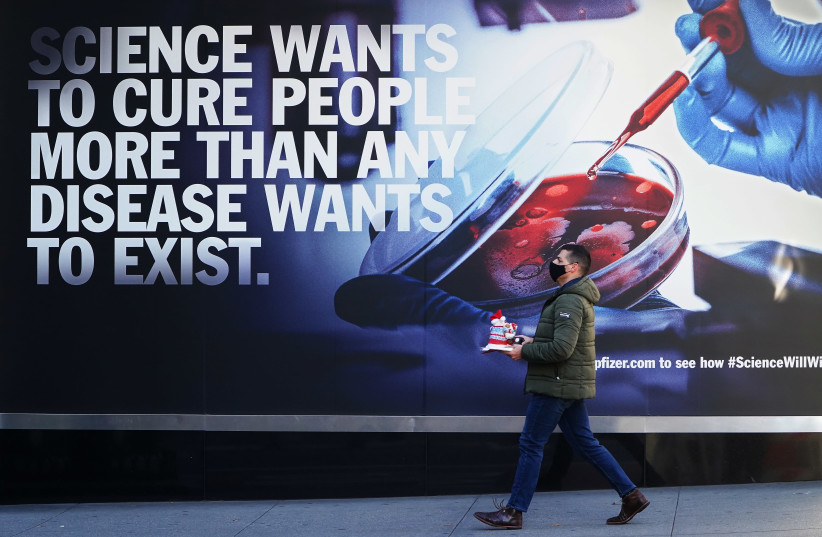 A person walks past the Pfizer Headquarters building in the Manhattan borough of New York City, New York, U.S., December 7, 2020 (photo credit: CARLO ALLEGRI/REUTERS)