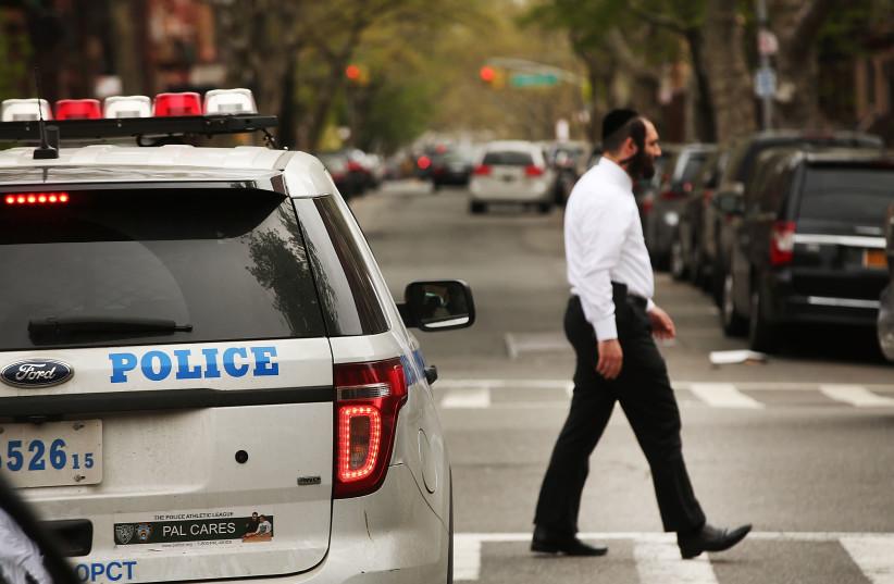 A Hasidic man walks by a police car in an Orthodox neighborhood in Brooklyn, April 24, 2017. (photo credit: SPENCER PLATT/GETTY IMAGES/JTA)