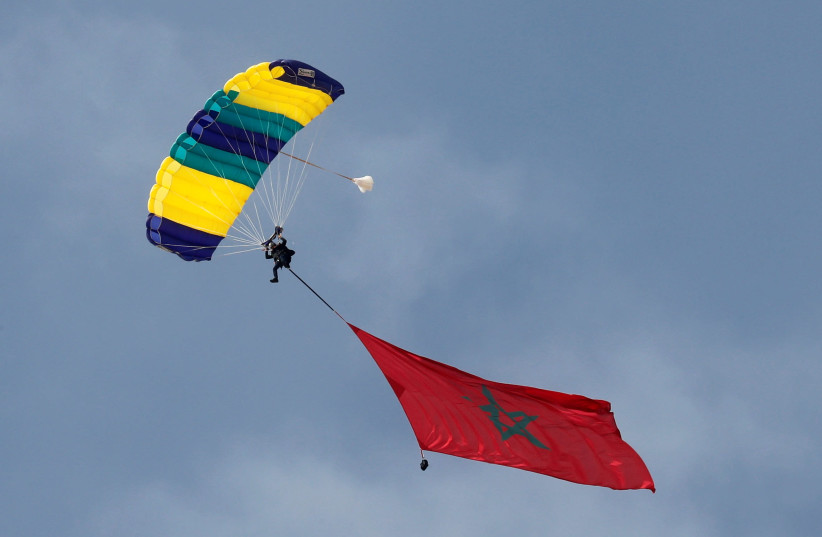 """A professional skydiver from Morocco carries the national flag as he flies over the pyramids of Giza during the international event """"Jump Like a Pharaoh"""", amid the coronavirus disease (COVID-19) outbreak, Giza, Egypt, November 8, 2020. (photo credit: AMR ABDALLAH DALSH / REUTERS)"""