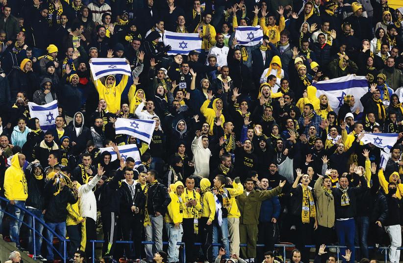 SUPPORTERS OF Beitar Jerusalem cheer for their team during a soccer match against Maccabi Umm el-Fahm  at Teddy Stadium in Jerusalem. (credit: NIR ELIAS / REUTERS)