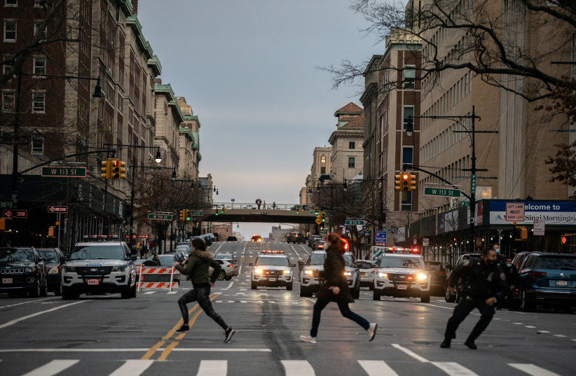 People run after a man opened fire outside the Cathedral Church of St. John the Divine in the Manhattan borough of New York City, New York, US, December 13, 2020. (photo credit: JEENAH MOON/REUTERS)