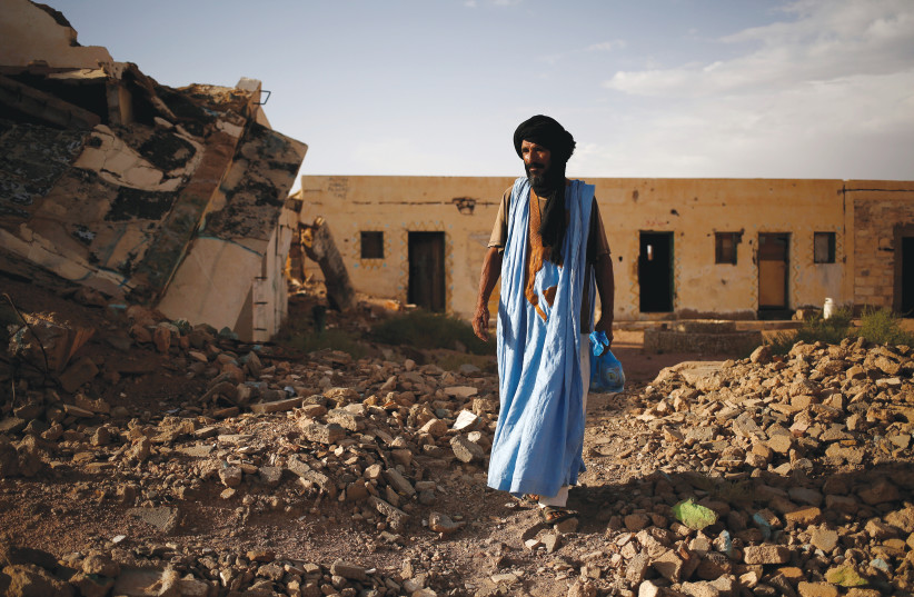A SOLDIER walks in Western Sahara in 2016, near ruins that were bombed in a war with Morocco more than 25 years ago. (photo credit: ZOHRA BENSEMRA/REUTERS)
