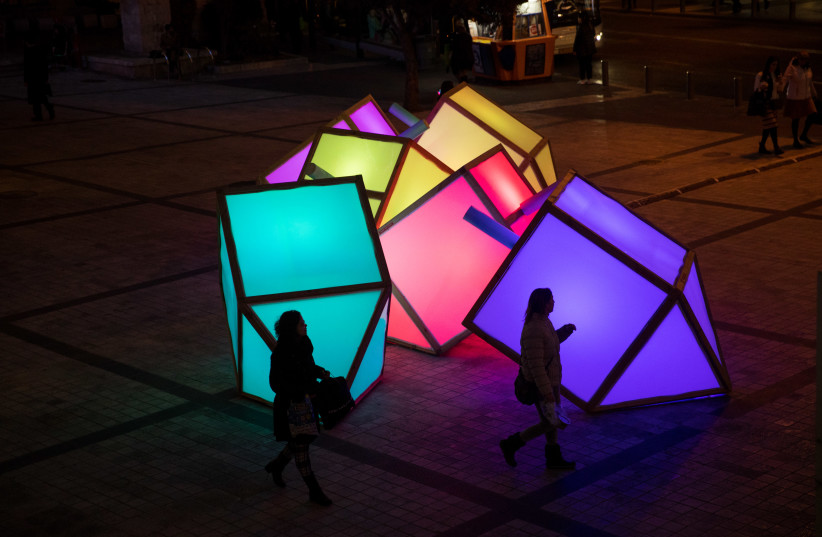 """People walk by large lit up """"sevivons"""", placed in Jerusalem, for the Jewish holiday of Hanukkah. The sevivon (dreidel) is a four-sided spinning top traditionally played with during Hanukkah, December 24, 2019. (photo credit: YONATAN SINDEL/FLASH90)"""