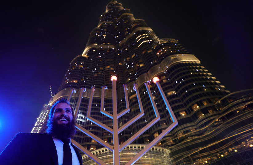 A man stands next to a giant menorah as people celebrate Hanukkah, the Jewish festival of lights, in Dubai, United Arab Emirates December 10, 2020. (photo credit: REUTERS/CHRISTOPHER PIKE)