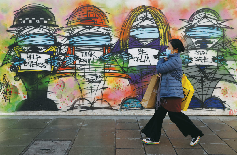 A woman wearing a face mask walks past coronavirus-related graffiti in central London in October. (photo credit: REUTERS/JOHN SIBLEY)