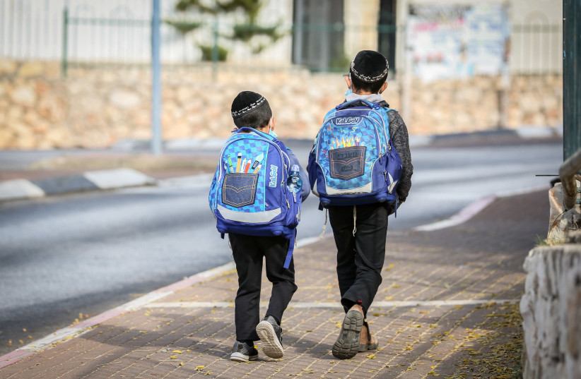 Israeli children wearing face masks make their way to school in Tzfat on their first day back to classes on November 1, 2020 (photo credit: DAVID COHEN/FLASH 90)