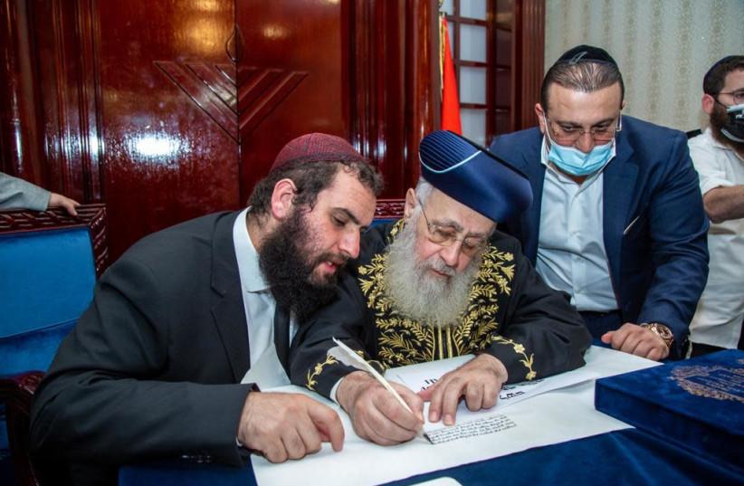 Israeli Chief Rabbi Yitzhak Yosef, center, writes part of a Torah scroll at the Jewish community center in Dubai, Dec. 19, 2020. At left is the center's leader, Rabbi Levi Duchman. (photo credit: COURTESY OF THE DUBAI JEWISH COMMUNITY CENTER)