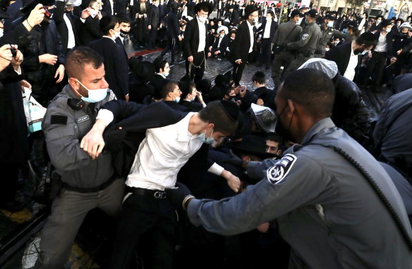 Police are seen forcibly dispersing haredi protesters gathered on Jaffa Street in Jerusalem on December 22, 2020. (photo credit: MARC ISRAEL SELLEM/THE JERUSALEM POST)