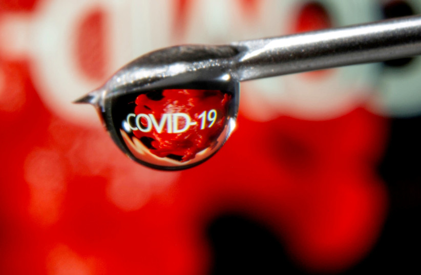 "The word ""COVID-19"" is reflected in a drop on a syringe needle in this illustration taken November 9, 2020.  (photo credit: REUTERS/DADO RUVIC/ILLUSTRATION/FILE PHOTO)"