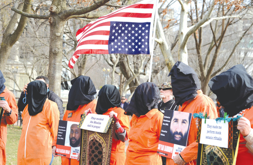 DEMONSTRATORS IN prison jumpsuits and black hoods call for the closure of the Guantanamo Bay detention camp, in a protest near the White House in January.  (photo credit: MIKE THEILER/REUTERS)