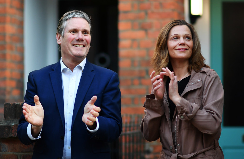 UK Labour leader Keir Starmer and his wife Victoria Starmer applaud for healthcare workers outside their home in London, May 14, 2020. (photo credit: JUSTIN SETTERFIELD/GETTY IMAGES)