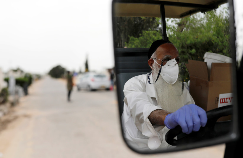 A WORKER reflected in his vehicle's mirror at a Tel Aviv cemetery in March, at a special center preparing bodies of Jews who died due to coronavirus. (photo credit: AMIR COHEN/REUTERS)
