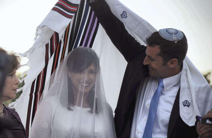 VEILED THEN-DEPUTY Transportation Minister Tzipi Hotovely stands with husband-to-be Or Alon at their 2013 wedding. Lester's tome discusses the symbolism of the veil and other aspects of nuptial ceremonies. (photo credit: YOSSI ZELIGER/FLASH90)