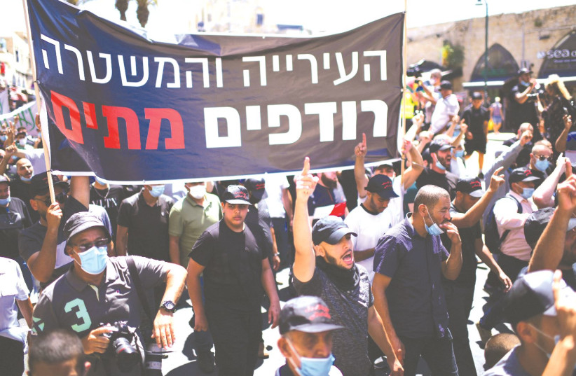 ARABS CITIZENS protest in Jaffa earlier this year, carrying a banner says that 'The city and the police are chasing after the dead' following a decision by the Tel Aviv Municipality to demolish an old Muslim burial ground which was discovered after plans had been made to build a homeless shelter and (photo credit: TOMER NEUBERG/FLASH90)