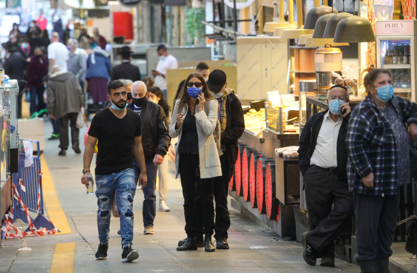 Israelis are seen walking in Jerusalem's Mahane Yehuda market amid the third coronavirus lockdown on New Year's Eve, December 31, 2020. (photo credit: MARC ISRAEL SELLEM/THE JERUSALEM POST)