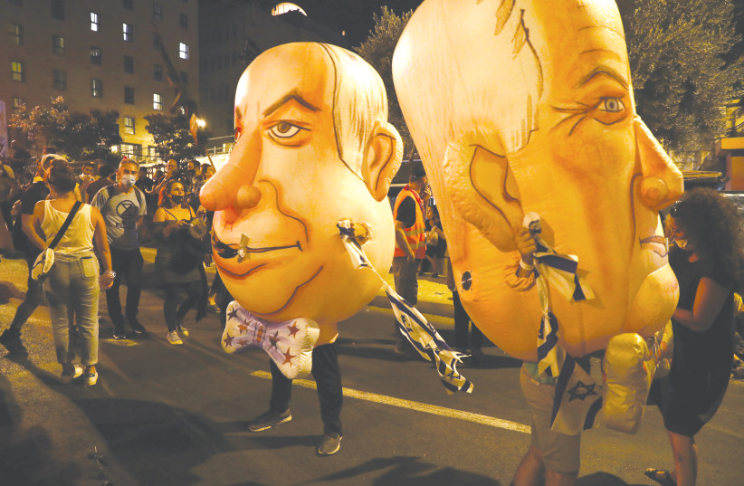 INFLATABLE COSTUMES depict Prime Minister Benjamin Netanyahu and his main coalition partner, Defense Minister Benny Gantz, at a demonstration in Jerusalem in August. (photo credit: AMMAR AWAD/REUTERS)