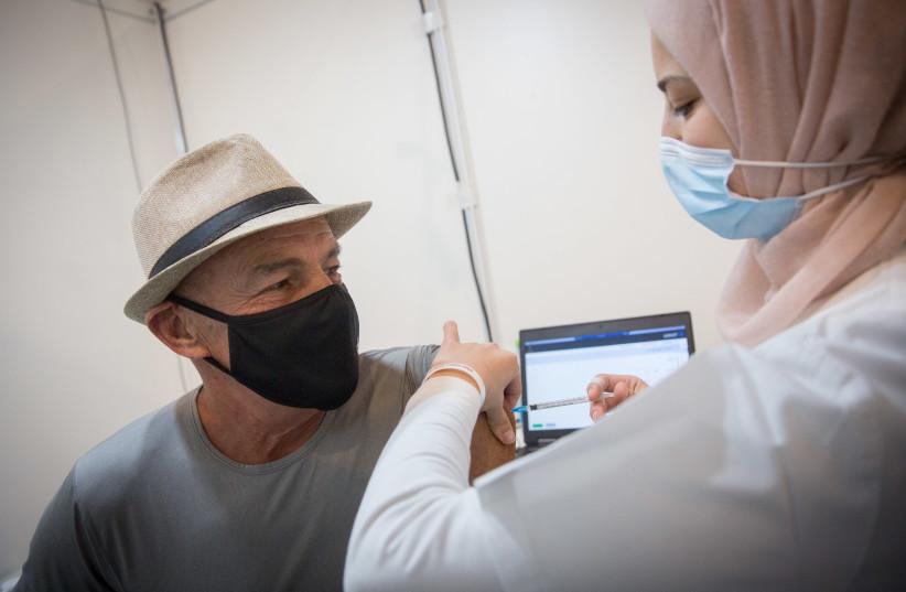 An Israeli man receives the coronavirus vaccine (photo credit: MIRIAM ALSTER/FLASH90)