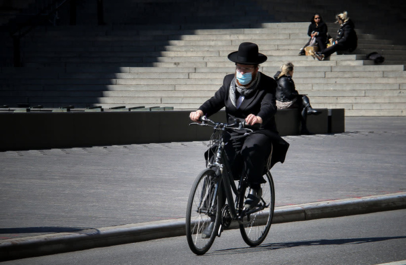 An Orthodox Jewish man wearing a surgical mask rides by the Metropolitan Museum of Art in New York City, April 22, 2020. (photo credit: ERICA PRICE/GETTY IMAGES)