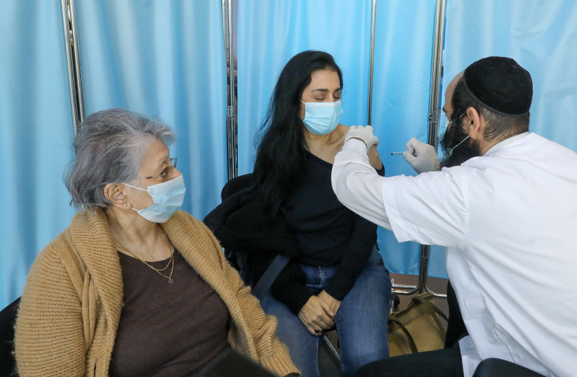 People get vaccinated at the Clalit vaccination center in Jerusalem, January 3, 2020. (photo credit: MARC ISRAEL SELLEM/THE JERUSALEM POST)
