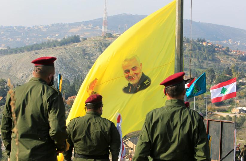 Des membres du Hezbollah libanais se tiennent près d'un drapeau avec une photo du haut commandant militaire iranien, le général Qassem Soleimani, lors d'une cérémonie marquant le premier anniversaire du meurtre de Soleimani et du commandant de la milice irakienne Abu Mahdi al-Muhandis lors d'une attaque américaine, dans le sud du Liban villag (crédit photo: REUTERS / AZIZ TAHER)