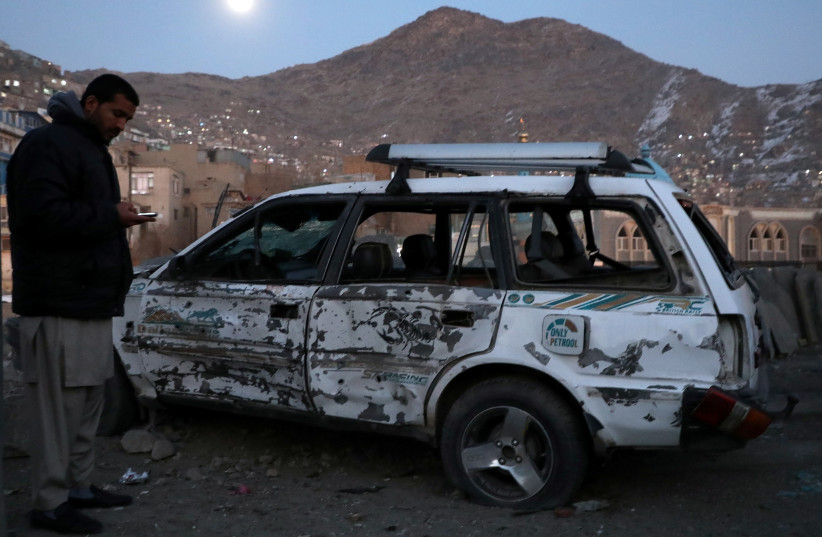 An Afghan man inspects a damaged car after a bomb blast in Kabul, Afghanistan December 28, 2020. (photo credit: OMAR SOBHANI / REUTERS)