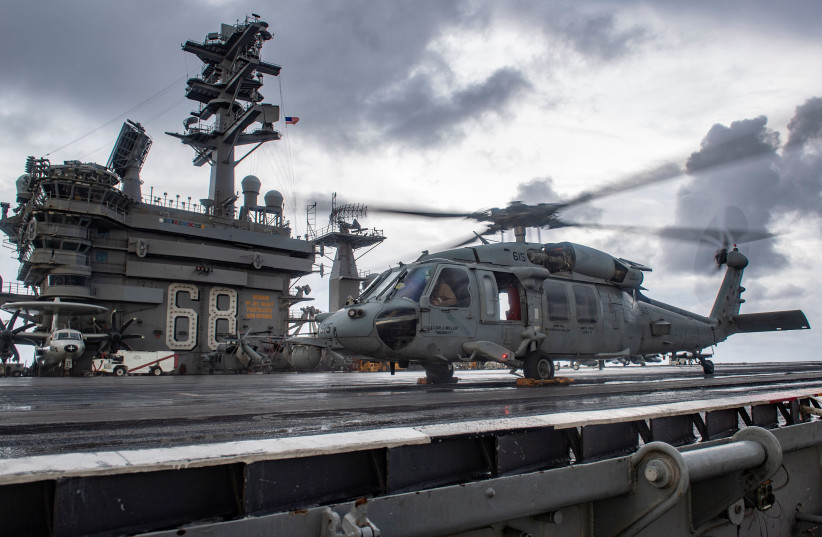 An MH-60S Sea Hawk helicopter conducts flight control checks on the flight deck of the U.S. Navy aircraft carrier USS Nimitz in the Indian Ocean November 25, 2020. Picture taken November 25, 2020 (photo credit: U.S. NAVY/MASS COMMUNICATION SPECIALIST 3RD CLASS ELLIOT SCHAUDT/HANDOUT VIA REUTERS)