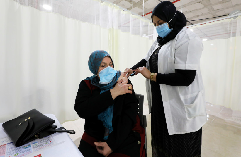 A woman receives a vaccination against the coronavirus disease (COVID-19) at a vaccination center in Umm El-Fahem, Israel January 3, 2021 (photo credit: REUTERS/AMMAR AWAD)