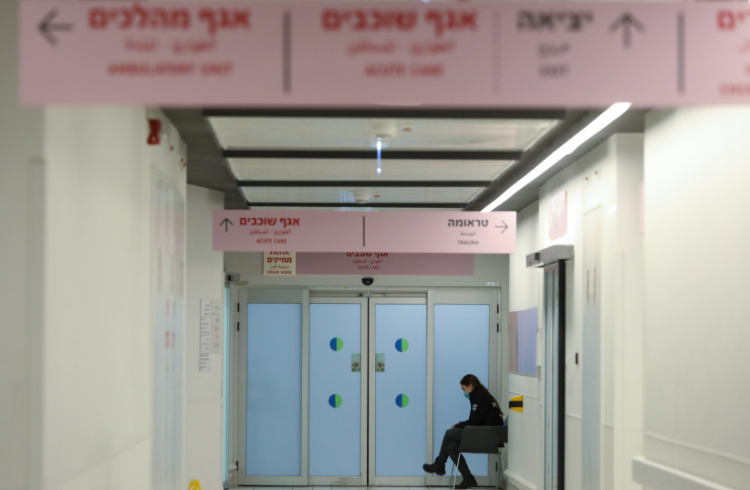 A woman is seen sitting in the hallway at Ashdod's Samson Assuta Hospital. (photo credit: MARC ISRAEL SELLEM/THE JERUSALEM POST)